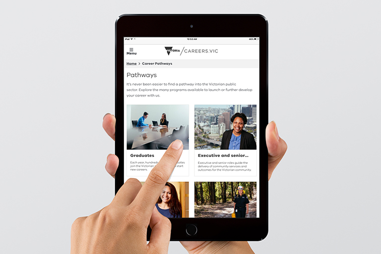 Hand holding a tablet device with Careers.vic website displayed