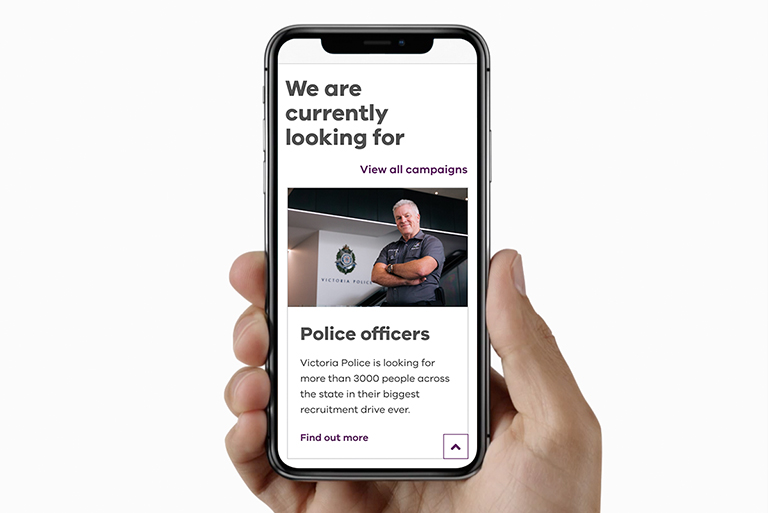 Hand holding a mobile phone with Careers.vic website displayed